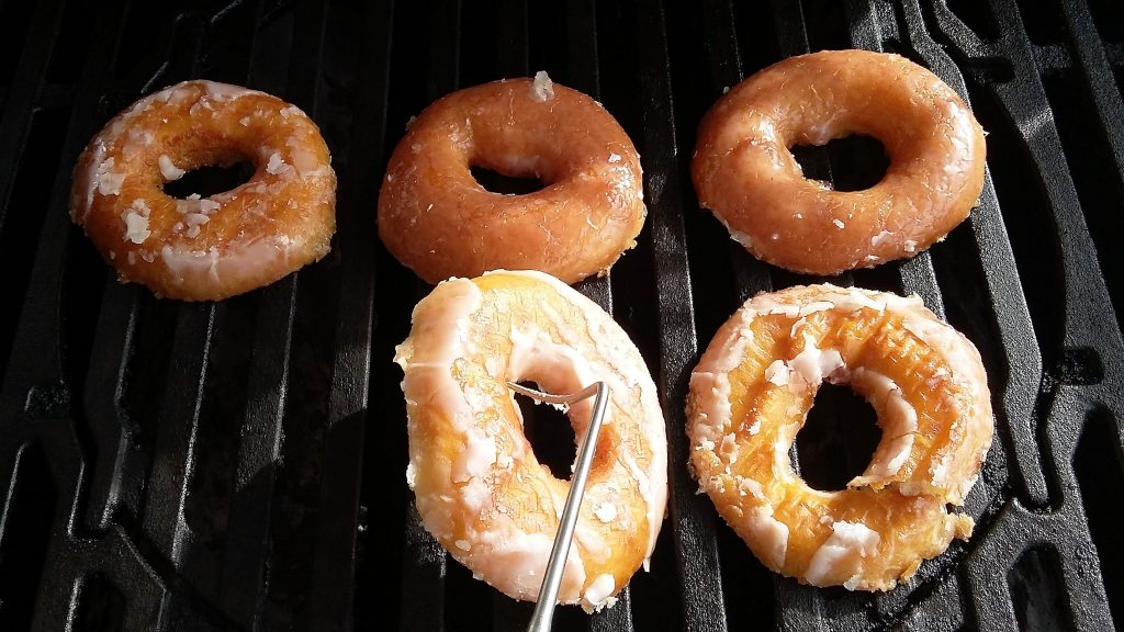 3 donuts halved on gas grill being turned