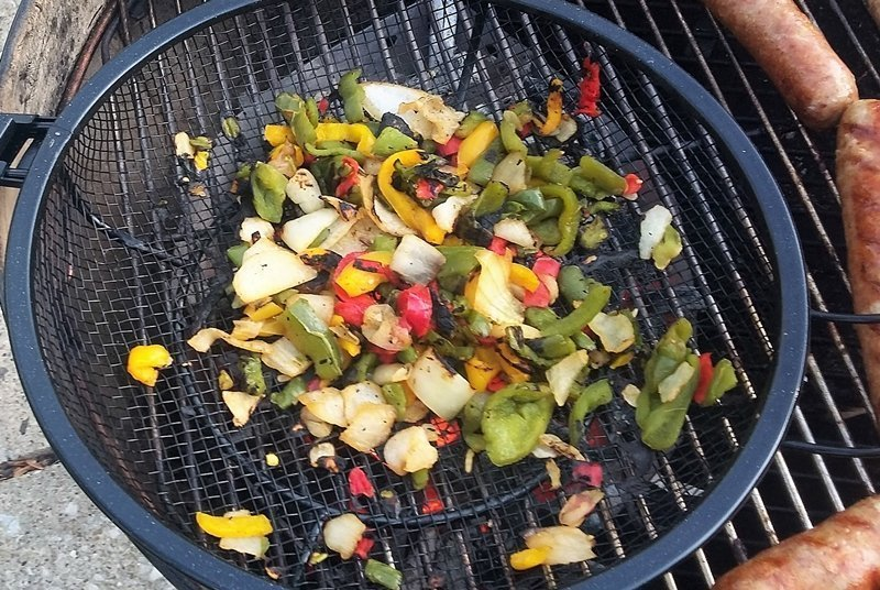 Charred frozen peppers and onions in grill basket on gas grill